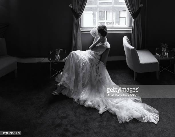 full length of bride standing by window at home - marriage stock pictures, royalty-free photos & images
