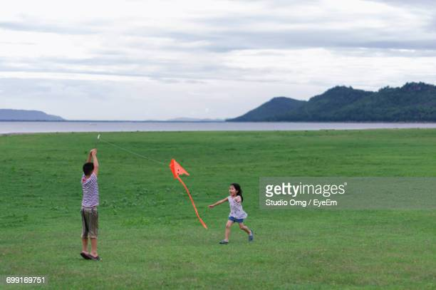 Full Length Of Brother And Sister Playing With Kite On Green Field Against Sky