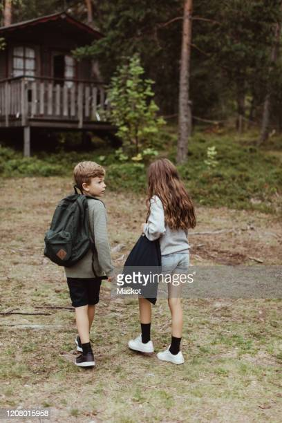 full length of brother and sister with bag standing against house in forest - 10歳から11歳 ストックフォトと画像