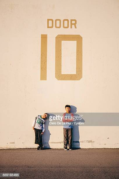 Full Length Of Brothers Standing Against Wall With Text On It