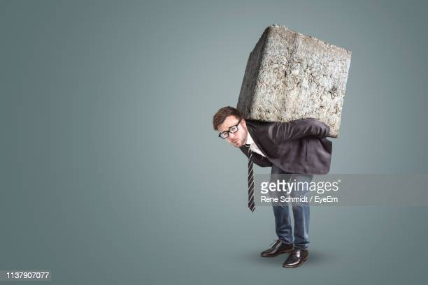 full length of businessman carrying cube shaped rock against gray background - tragen stock-fotos und bilder