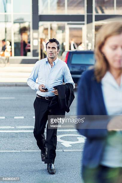 Full length of businessman crossing city street
