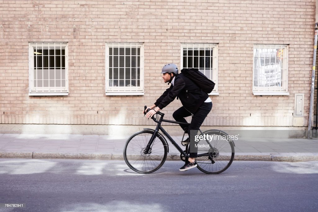 Full length of businessman cycling on street by building in city : Foto de stock