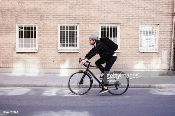 full length of businessman cycling on street by building in city - sportschutzhelm stock-fotos und bilder