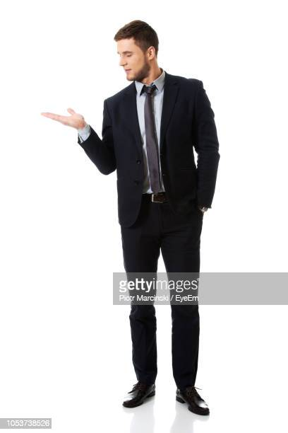 full length of businessman gesturing while standing against white background - abbigliamento elegante foto e immagini stock