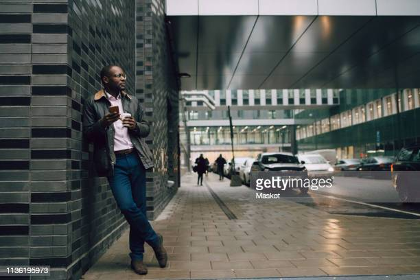 full length of businessman holding coffee and mobile phone looking away while standing on road in city - 背景に人 ストックフォトと画像