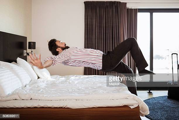 Full length of businessman jumping on bed in hotel room