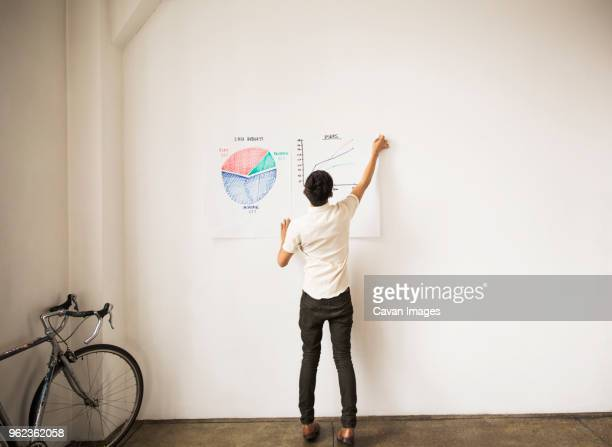 full length of businessman sticking graphs on white wall at creative office - lever la main photos et images de collection