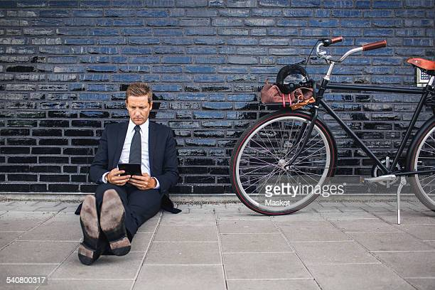 Full length of businessman using digital tablet while sitting on sidewalk by bicycle