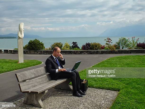 Full Length Of Businessman Using Laptop While Sitting On Bench Against Sea