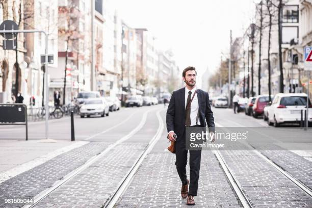 full length of businessman walking by railroad tracks in city - full suit stock pictures, royalty-free photos & images