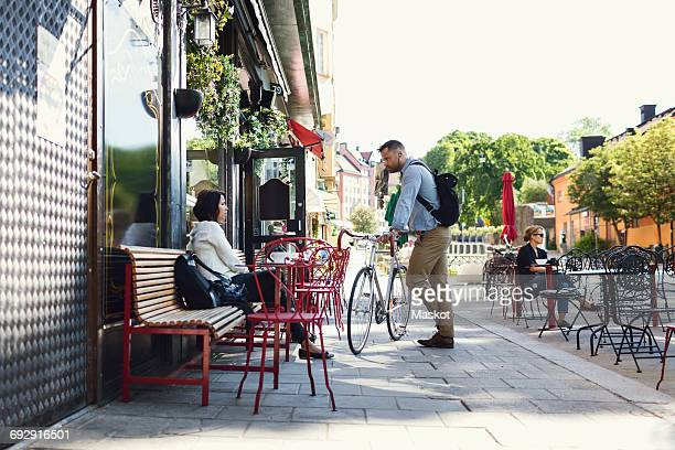 full length of businessman with bicycle talking to colleague at sidewalk cafe - pavement cafe stock pictures, royalty-free photos & images