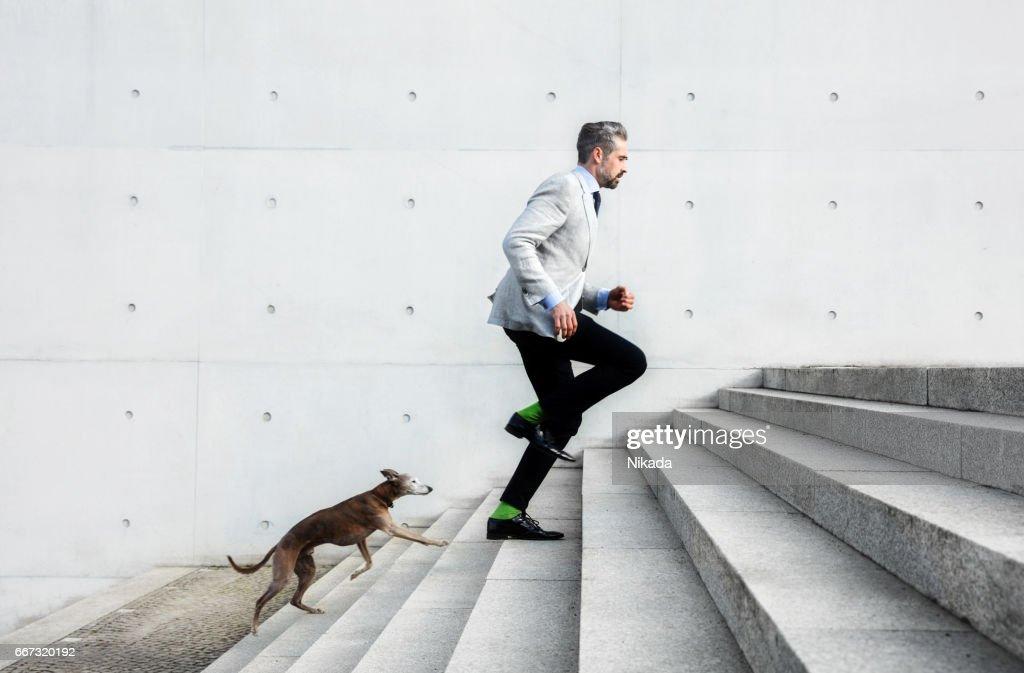 Full length of businessmen running on steps with dog : Stock Photo