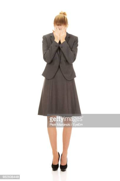 Full Length Of Businesswoman Covering Her Face While Standing Against White Background