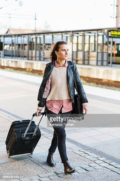 full length of businesswoman pulling wheeled luggage while walking on railroad station platform - wheeled luggage stock photos and pictures