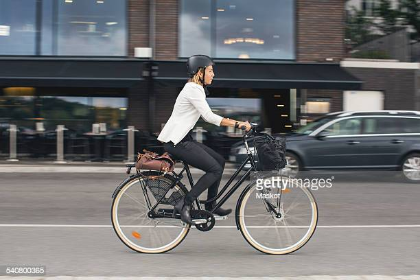full length of businesswoman riding bicycle on city street - city life photos et images de collection