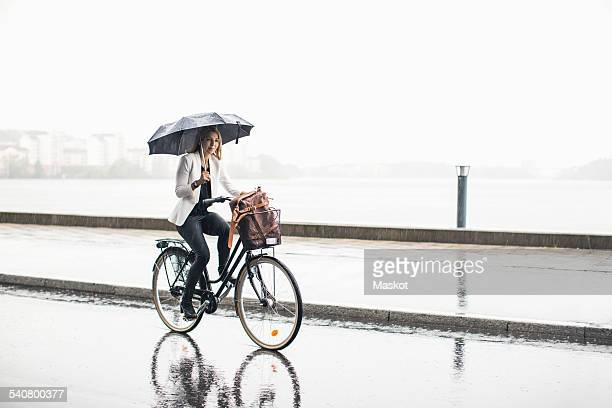 Full length of businesswoman riding bicycle on wet city street during rainy season