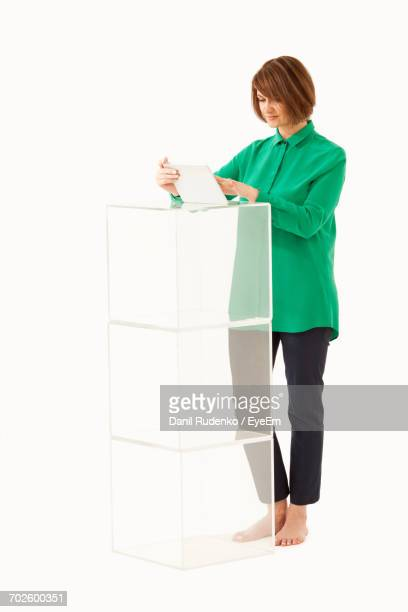 Full Length Of Businesswoman Using Digital Tablet While Standing By Blocks Against White Background