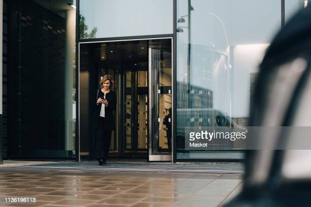 full length of businesswoman using smart phone while leaving from office - leaving fotografías e imágenes de stock