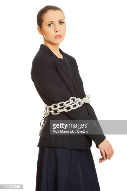 full length of businesswoman with chain tied on hands against white background - bound in high heels foto e immagini stock