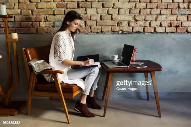 full length of businesswoman working at hotel lobby - 若い女性だけ ストックフォトと画像