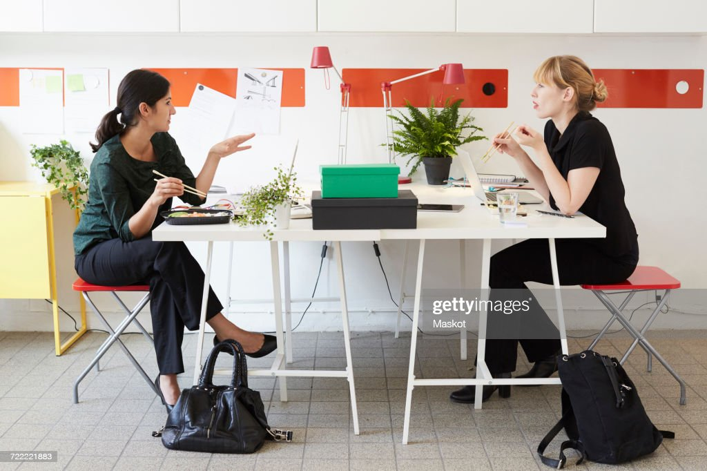 Full length of businesswomen talking while having lunch at table in office : ストックフォト