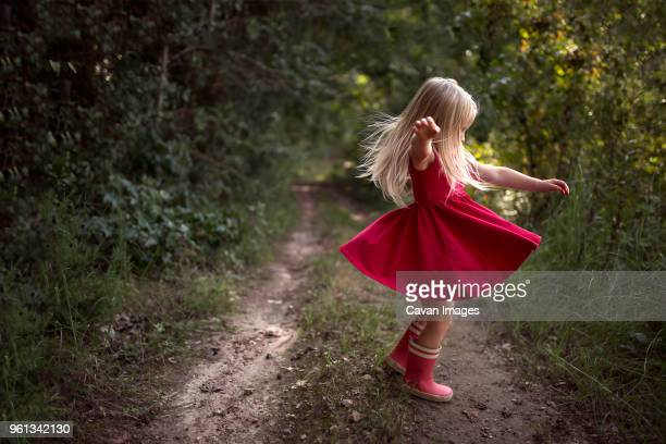full length of carefree girl spinning at forest - pink dress stock pictures, royalty-free photos & images