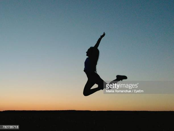 Full Length Of Cheerful Silhouette Woman Jumping Over Field Against Clear Sky During Sunset