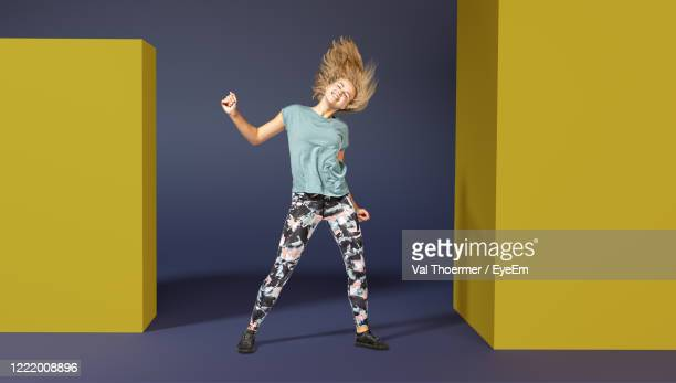 full length of cheerful woman dancing against blue background - val thoermer stock-fotos und bilder