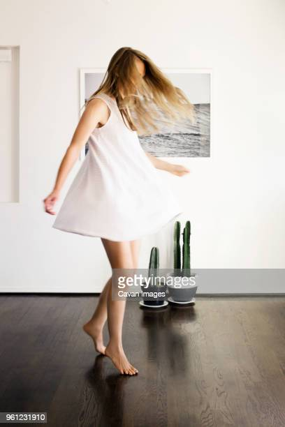 full length of cheerful woman dancing at home - kleid stock-fotos und bilder