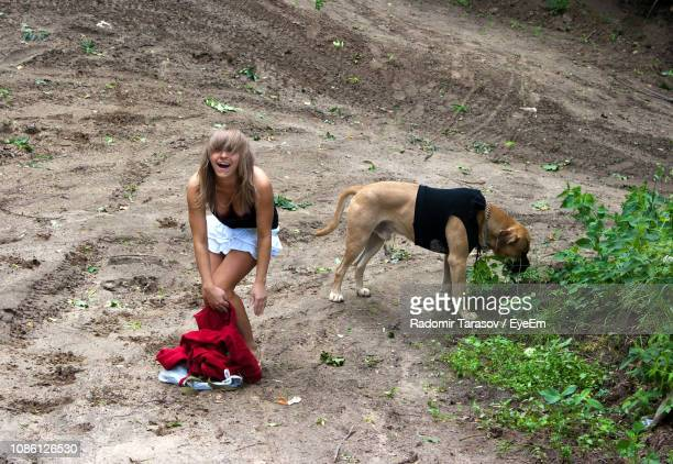 full length of cheerful woman standing by dog on dirt - animal costume stock pictures, royalty-free photos & images
