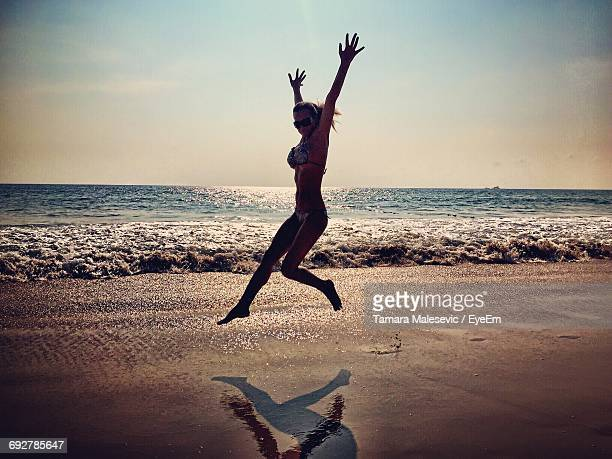 Full Length Of Cheerful Young Woman Jumping At Beach