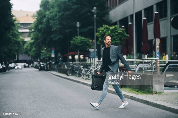 full length of confident businessman looking away crossing street in city - 歩く ストックフォトと画像