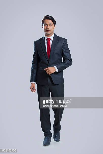 Full length of confident businessman walking against gray background