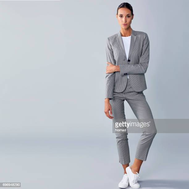full length of confident businesswoman holding arm - suit stock pictures, royalty-free photos & images