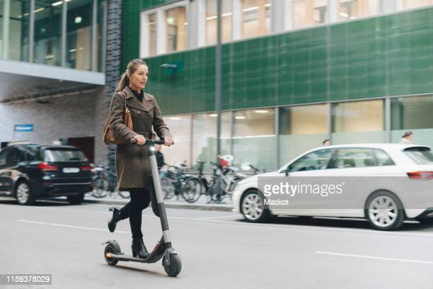 full length of confident businesswoman riding electric push scooter on street in city - onderweg stockfoto's en -beelden