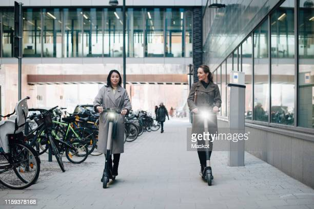 full length of confident female colleagues riding electric push scooter on footpath by building in city - electric scooter stock pictures, royalty-free photos & images