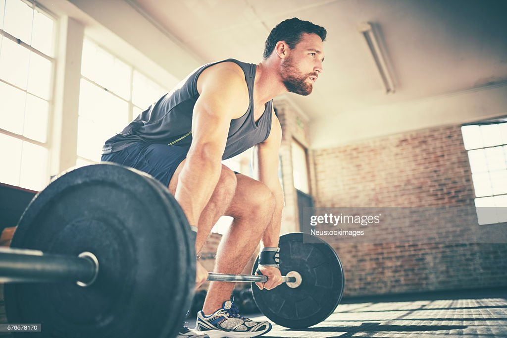 Full length of confident man dead lifting barbell in gym : Stock Photo