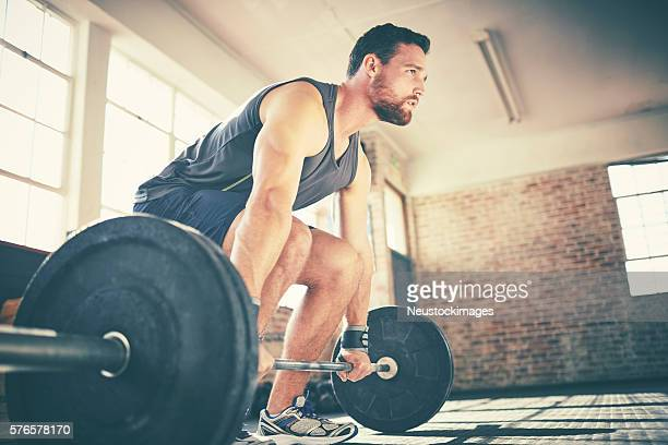 Full length of confident man dead lifting barbell in gym
