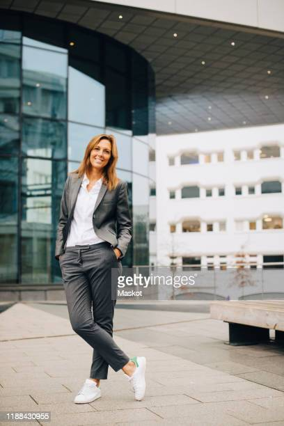 full length of confident smiling businesswoman standing against glass building - three quarter length stock pictures, royalty-free photos & images