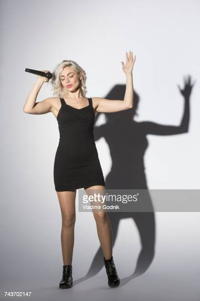 Full length of confident woman singing with microphone while gesturing against white background