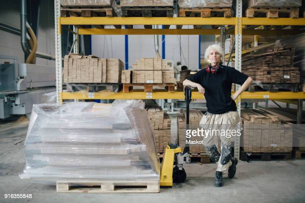 Full length of confident worker standing by stacked planks on pallet jack at industry