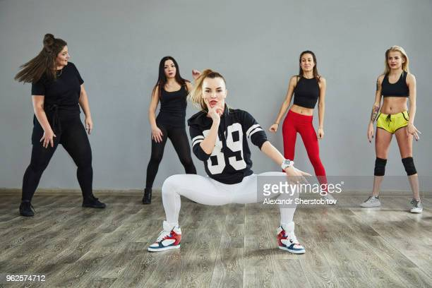 Full length of confident young dancers dancing against wall at studio