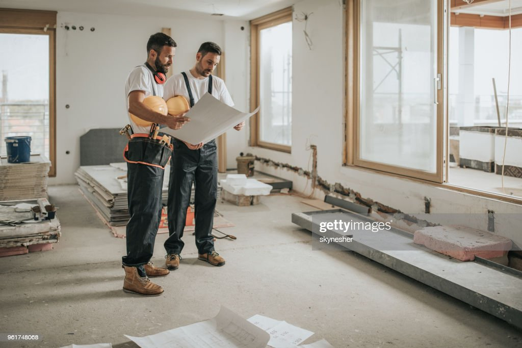 Full length of construction workers analyzing blueprints in the apartment. : Stock Photo