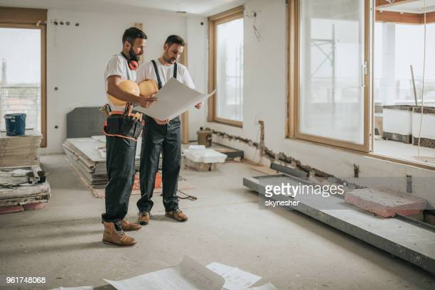 full length of construction workers analyzing blueprints in the apartment. - reform stock pictures, royalty-free photos & images