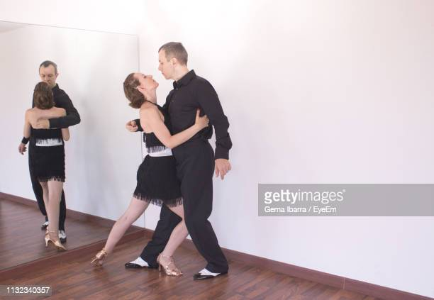 full length of couple dancing at studio - salsa dancing stock photos and pictures