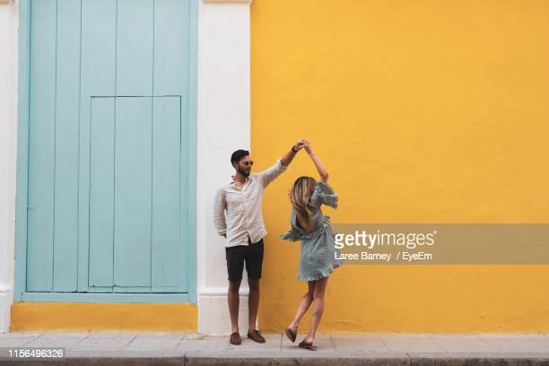 full length of couple dancing on sidewalk against yellow wall - young couple stock pictures, royalty-free photos & images