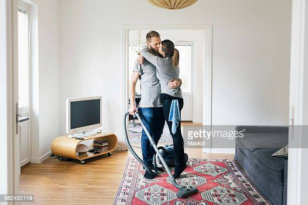 full length of couple kissing while cleaning home - heteroseksueel koppel stockfoto's en -beelden