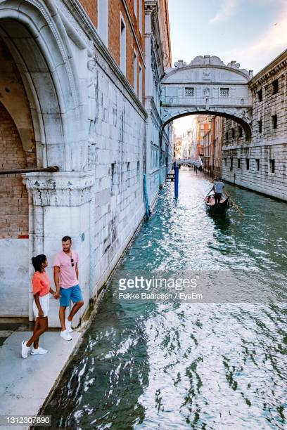 full length of couple standing by canal - mid adult stock pictures, royalty-free photos & images