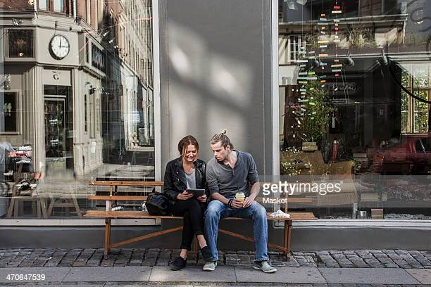 Full length of couple using digital tablet together on sidewalk bench